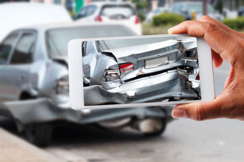 insurance agent using a smartphone to photograph auto accident damage